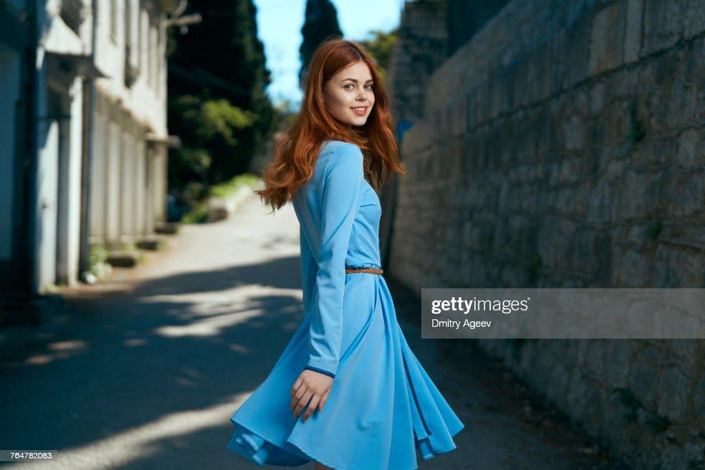 Smiling Caucasian woman near stone wall : Stock-Foto
