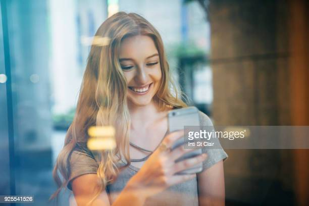 Smiling Caucasian woman posing for cell phone selfie behind window