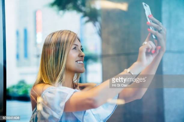 Smiling Caucasian woman posing for cell phone selfie
