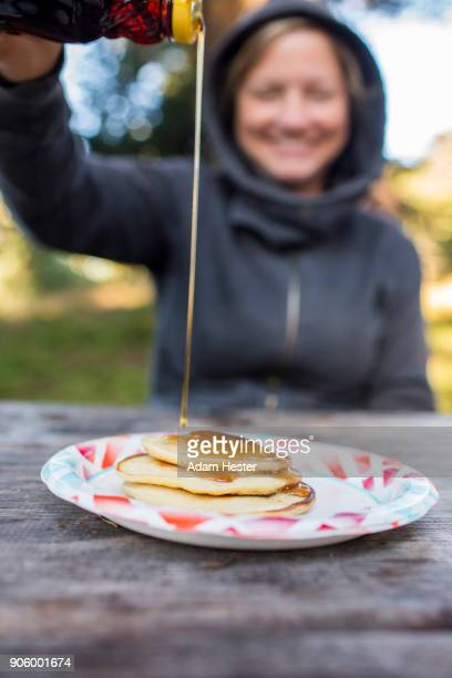 Smiling Caucasian woman pouring syrup on pancakes
