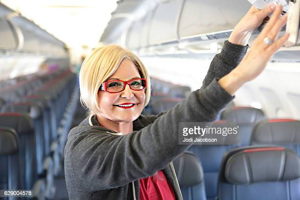 Smiling caucasian woman puts luggag in overhead bin on airplane