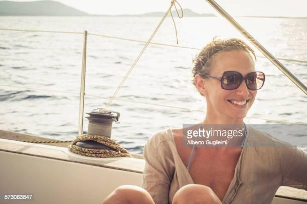 smiling caucasian woman sitting on boat deck - einzelne frau über 30 stock-fotos und bilder