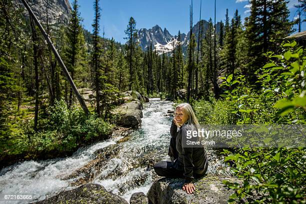 Smiling Caucasian woman sitting on rock at mountain river