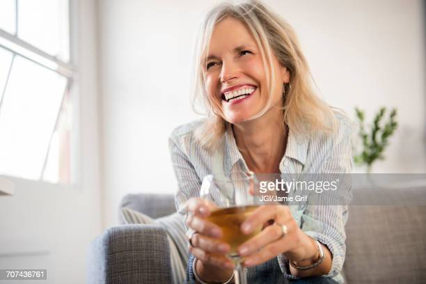 smiling caucasian woman sitting on sofa drinking white wine - drinking stock pictures, royalty-free photos & images