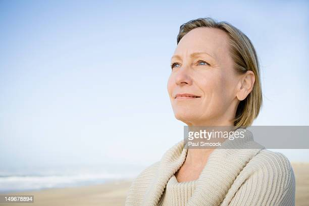 Smiling Caucasian woman standing on beach