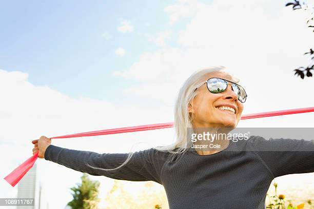 smiling caucasian woman stretching with resistance band - baby boomer stock pictures, royalty-free photos & images