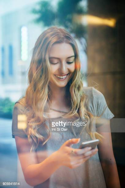 Smiling Caucasian woman texting on cell phone behind window