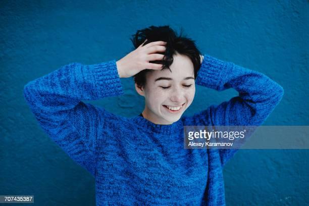 Smiling Caucasian woman tousling hair near blue wall