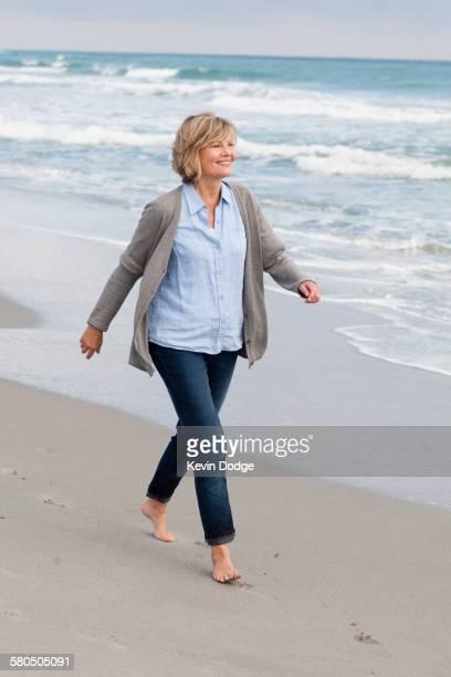 smiling caucasian woman walking on beach - frau 65 jahre stock-fotos und bilder