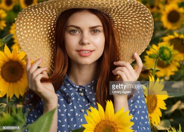Smiling Caucasian woman wearing hat in field of sunflowers