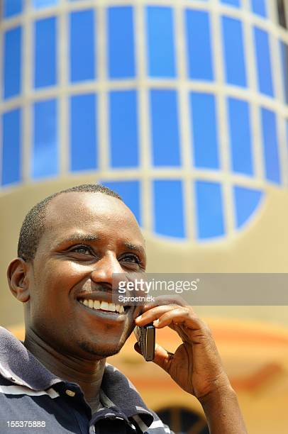 smiling central african male using mobile phone - east africa stock photos and pictures