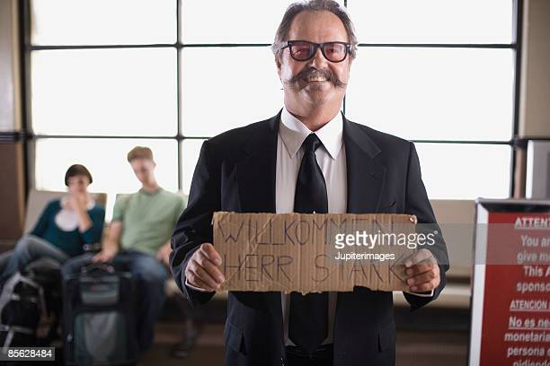 Smiling chauffeur holding German sign in airport