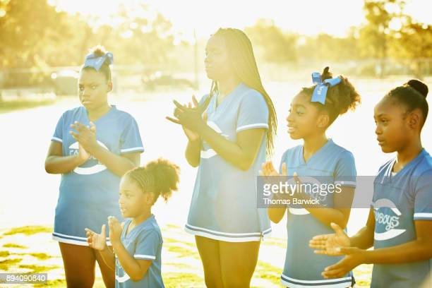 smiling cheerleaders clapping together while practicing routine during early morning workout - black cheerleaders stock photos and pictures