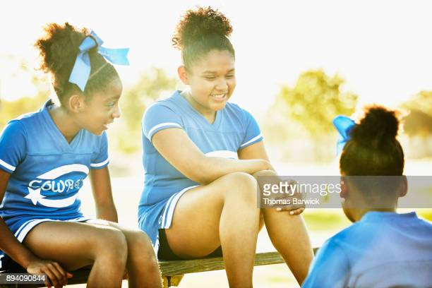 smiling cheerleaders hanging out together on bleachers after morning workout - black cheerleaders stock photos and pictures