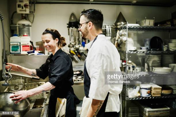 Smiling chef and dishwasher in discussion in restaurant kitchen