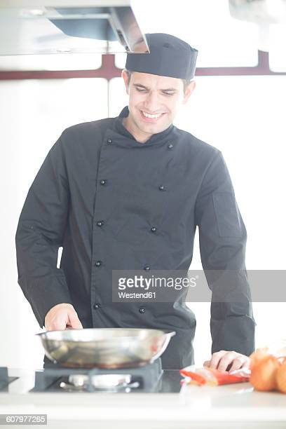 Smiling chef cooking in kitchen