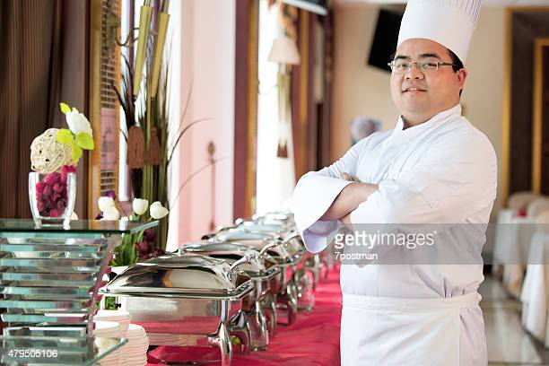 Smiling Chef In Uniform Standing Arms Crossed
