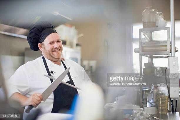 Smiling chef sharpening knife in kitchen