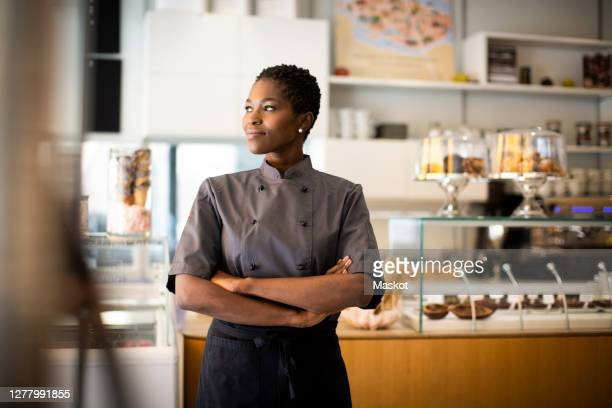 smiling chef with arms crossed looking away in chocolate factory - owner stock pictures, royalty-free photos & images