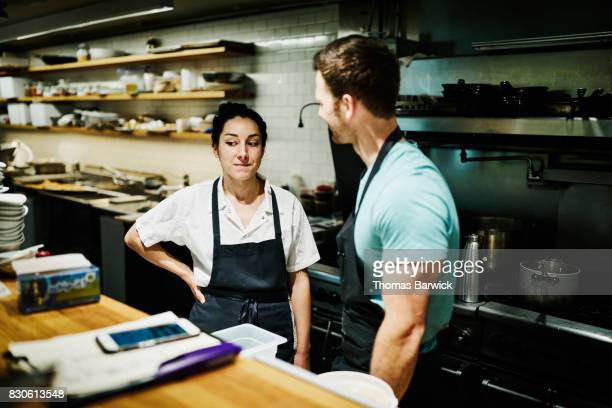 Smiling chefs in discussion in restaurant kitchen while preparing for dinner service