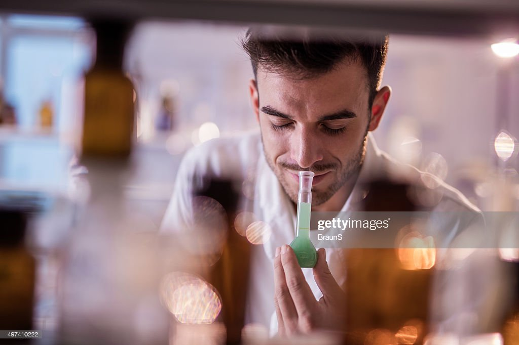 Smiling chemist smelling substances from a beaker in a laboratory. : Stock Photo