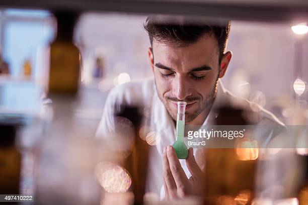 Smiling chemist smelling substances from a beaker in a laboratory.