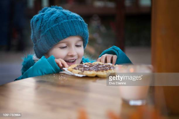 smiling child eating sweet food at a high table at a street food market - hoofddeksel stockfoto's en -beelden