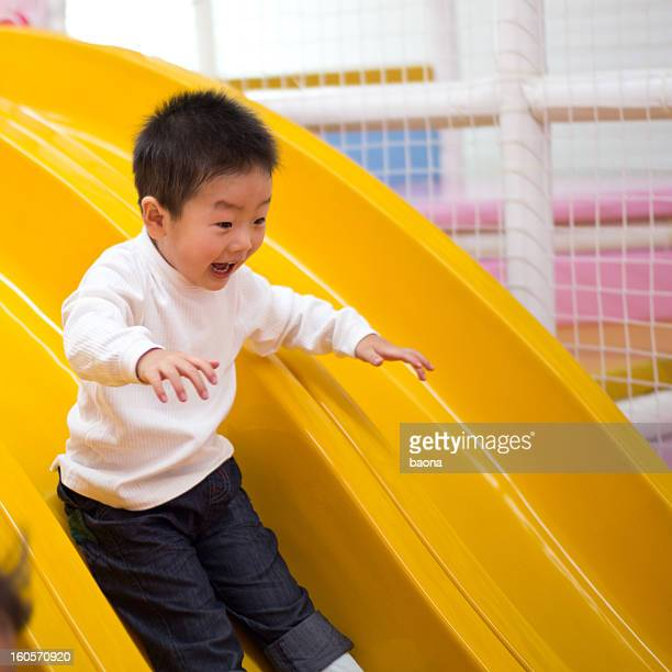 Smiling child going down a yellow slide
