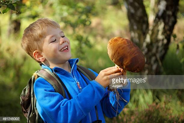 smiling child holding a big boletus mushroom in the forest - vinden stockfoto's en -beelden