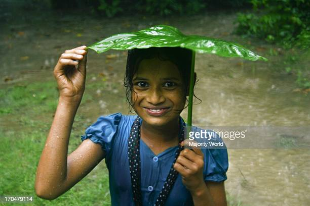 Smiling child in the rain at a village in Munshiganj, in Bangladesh. July 1, 2009.
