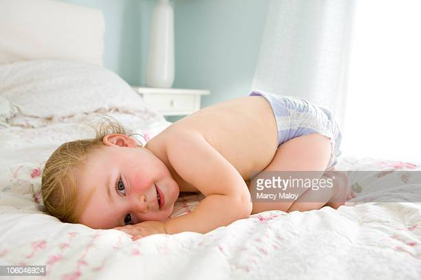 smiling child on bed wearing a purple diaper