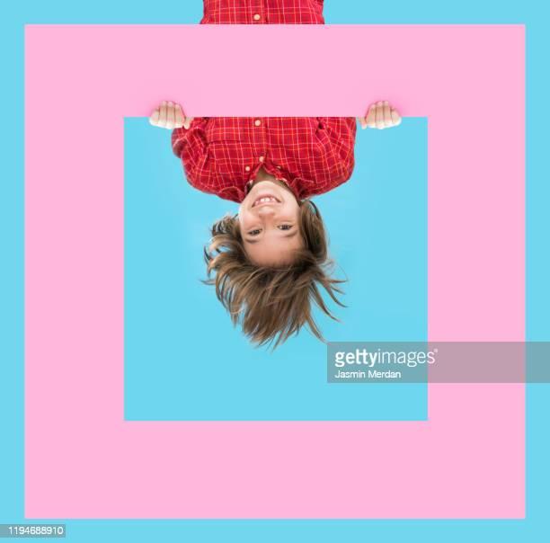 smiling child on blue background with colorful frame design shapes - auf den kopf gestellt stock-fotos und bilder