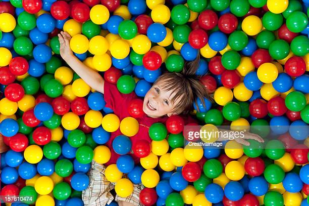 Smiling child playing in a colorful ball pit