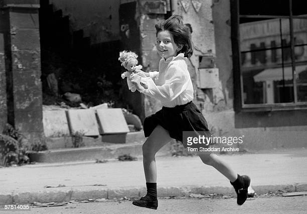 A smiling child runs across 'Sniper Alley' in Sarajevo during heavy fighting in 1993