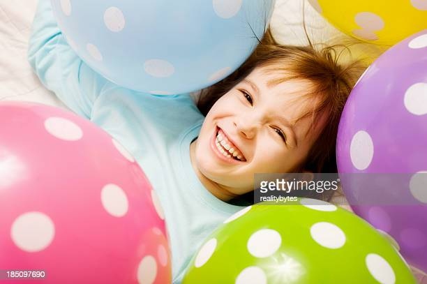Smiling child surrounded by polka dot balloons