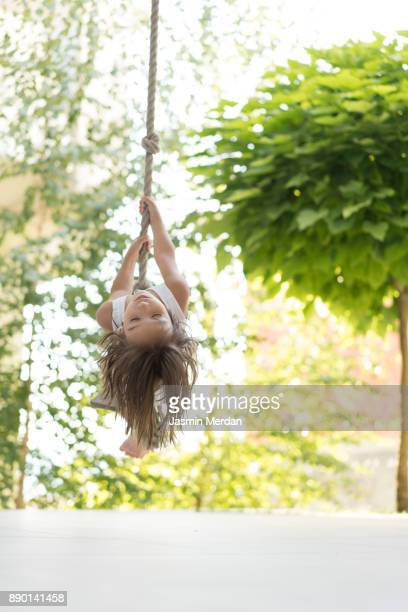 smiling child swinging on rope at playground - schommelen bungelen stockfoto's en -beelden