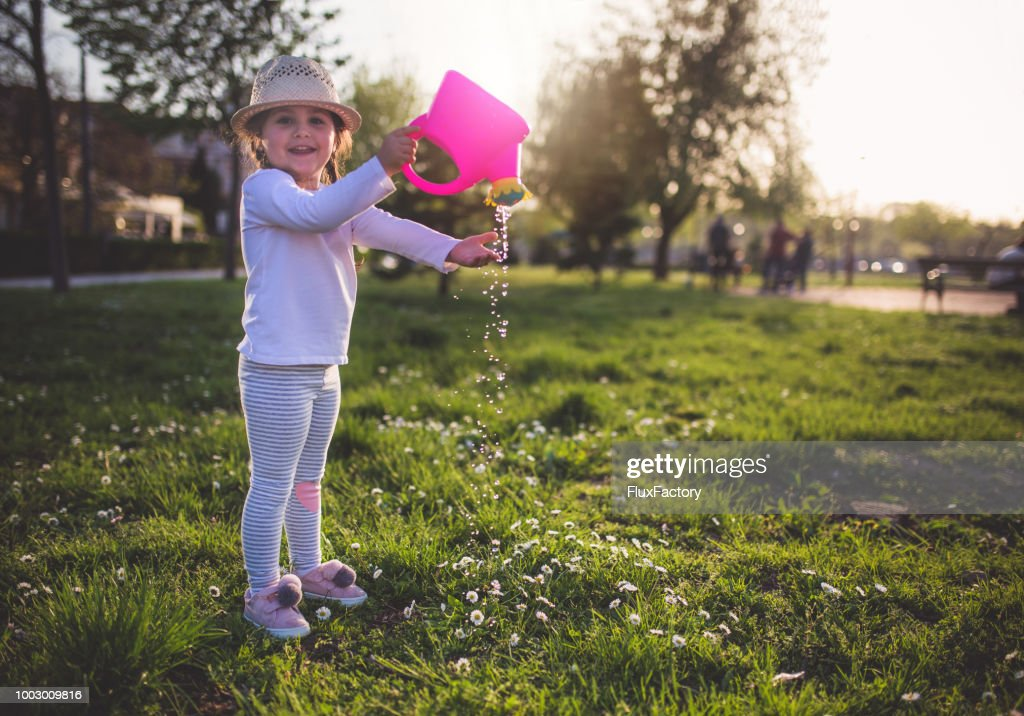 Smiling Child Watering Plants Stock Photo