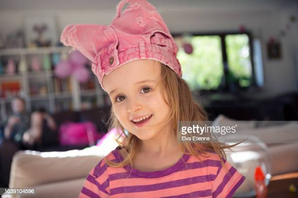 Smiling child with a pair of shorts on her head
