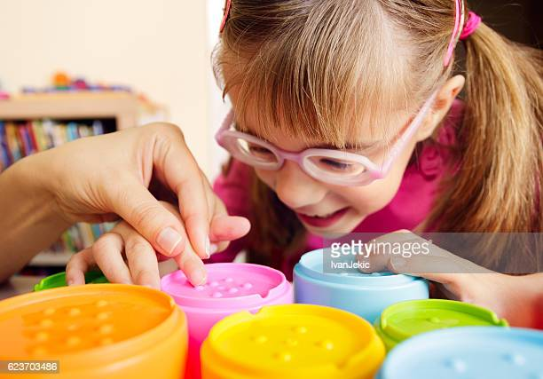 smiling child with disability touching textured cups with her teacher - 視覚障害 ストックフォトと画像