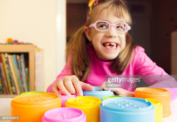 Smiling child with poor vision playing with tactile toys