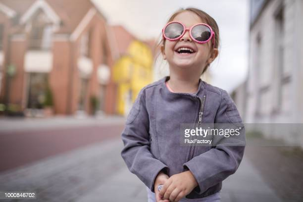 smiling child with sunglasses on a street - innocence stock pictures, royalty-free photos & images