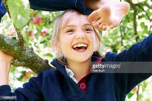 Smiling children climbing tree together