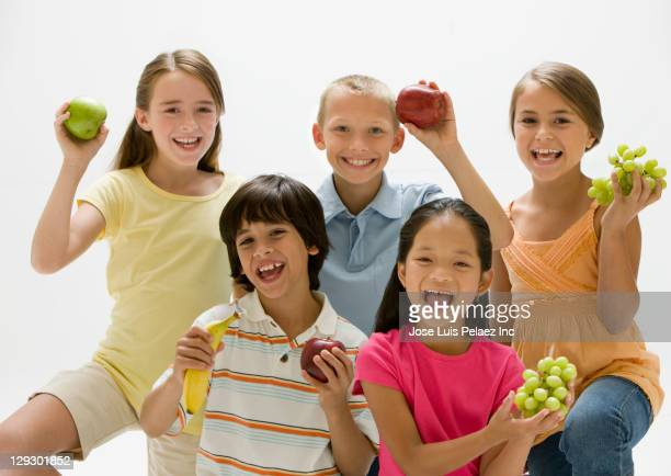 smiling children holding fresh fruit - kid girl eating apple stock photos and pictures