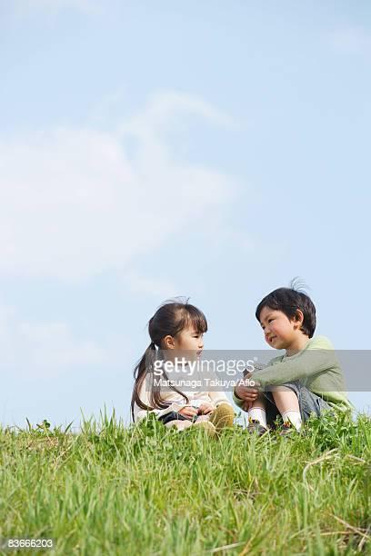 Smiling children talking in park