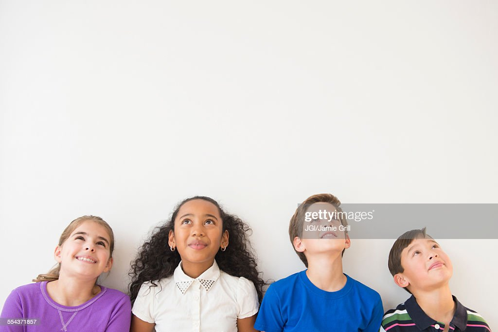 Smiling children thinking and looking up : Stock Photo