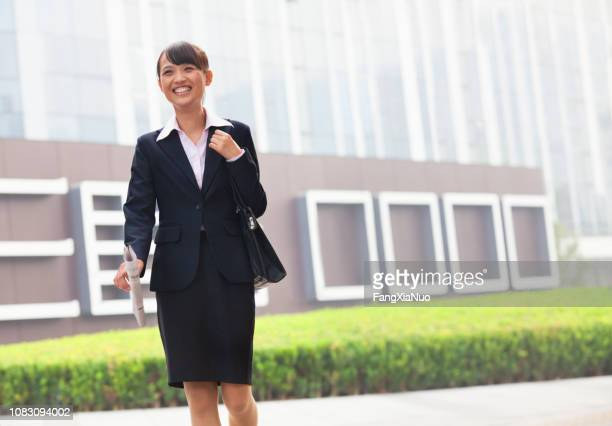 smiling chinese businesswoman walking - day 1 stock pictures, royalty-free photos & images