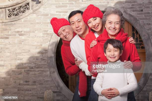 smiling chinese family celebrating new year - chinese new year stock pictures, royalty-free photos & images