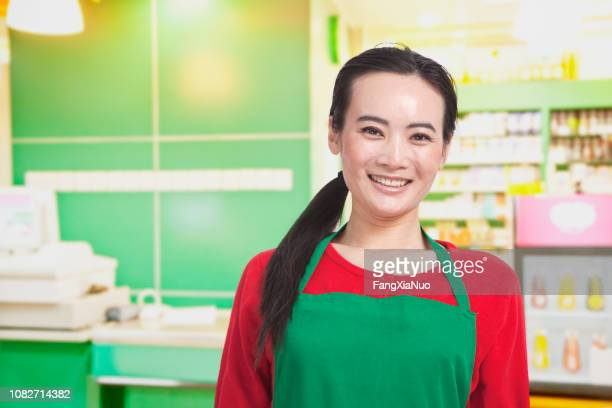 smiling chinese grocery store worker - hair back stock pictures, royalty-free photos & images