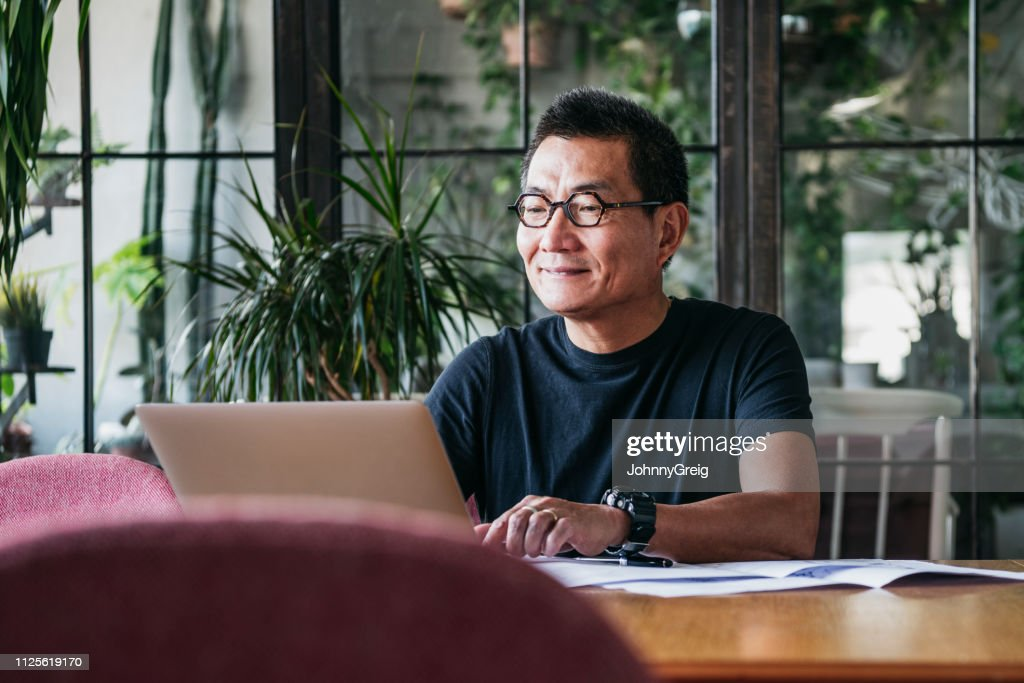 Smiling Chinese man working on laptop at home : Stock Photo