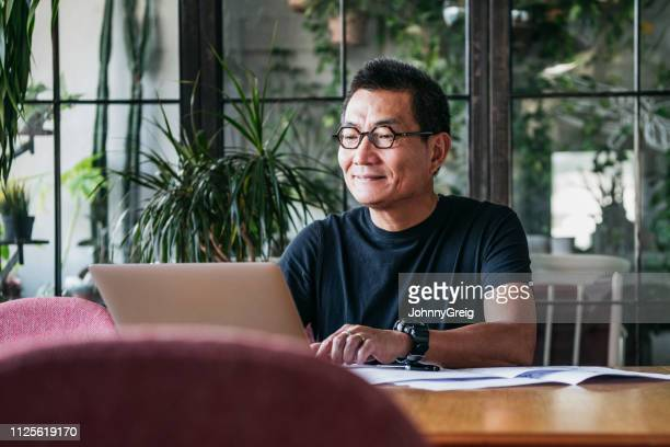 smiling chinese man working on laptop at home - working from home stock pictures, royalty-free photos & images